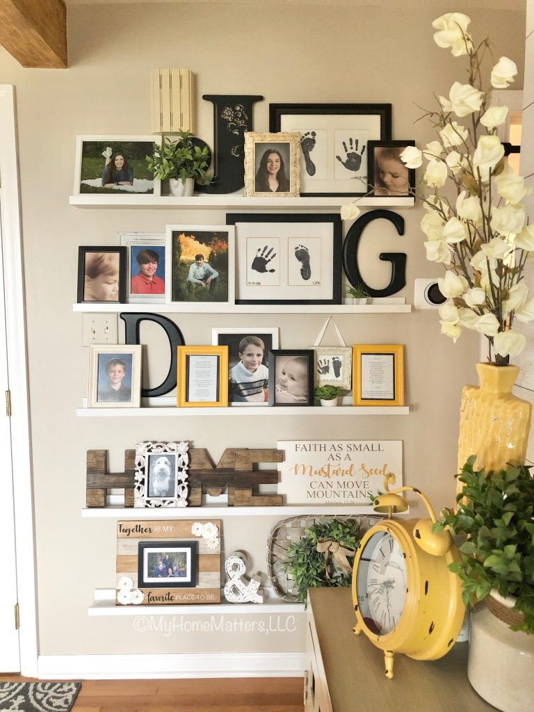 a gallery wall of family photos in an entry hall