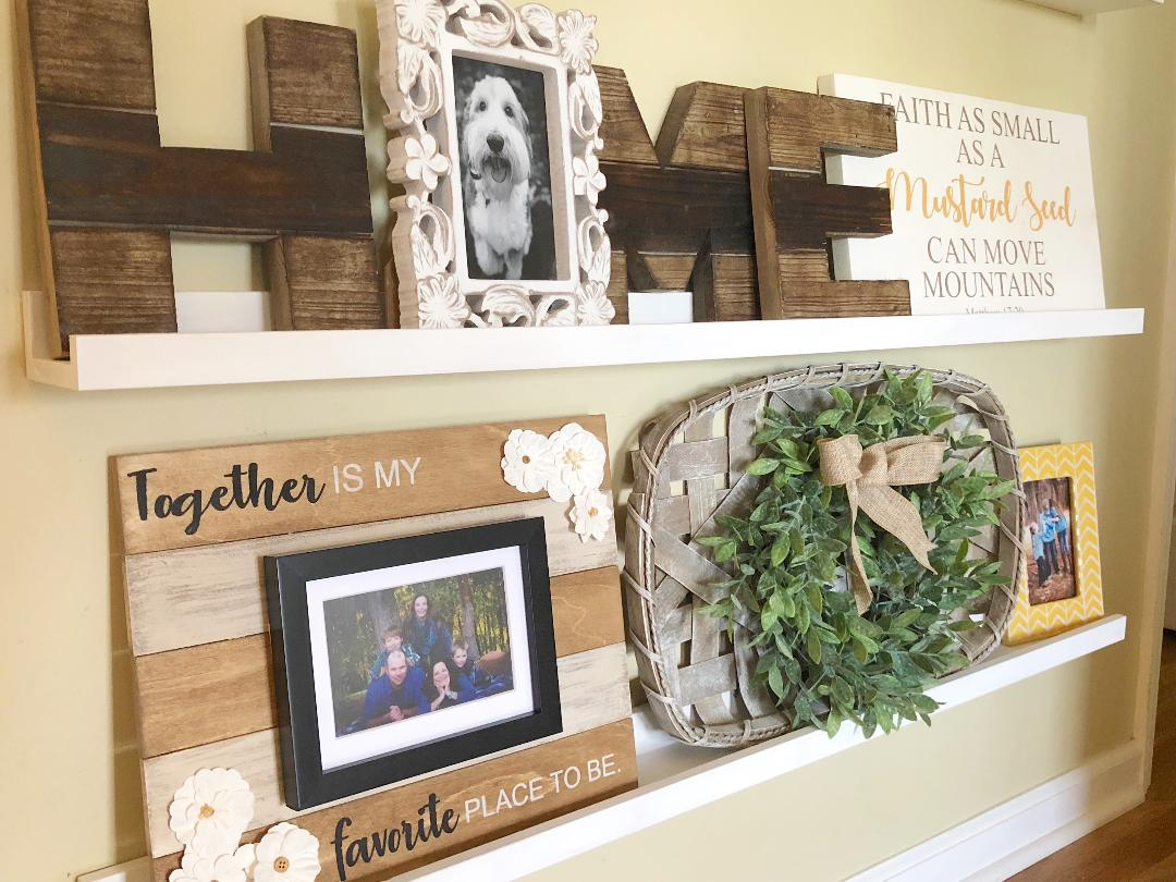 a gallery wall with home decor and family photos