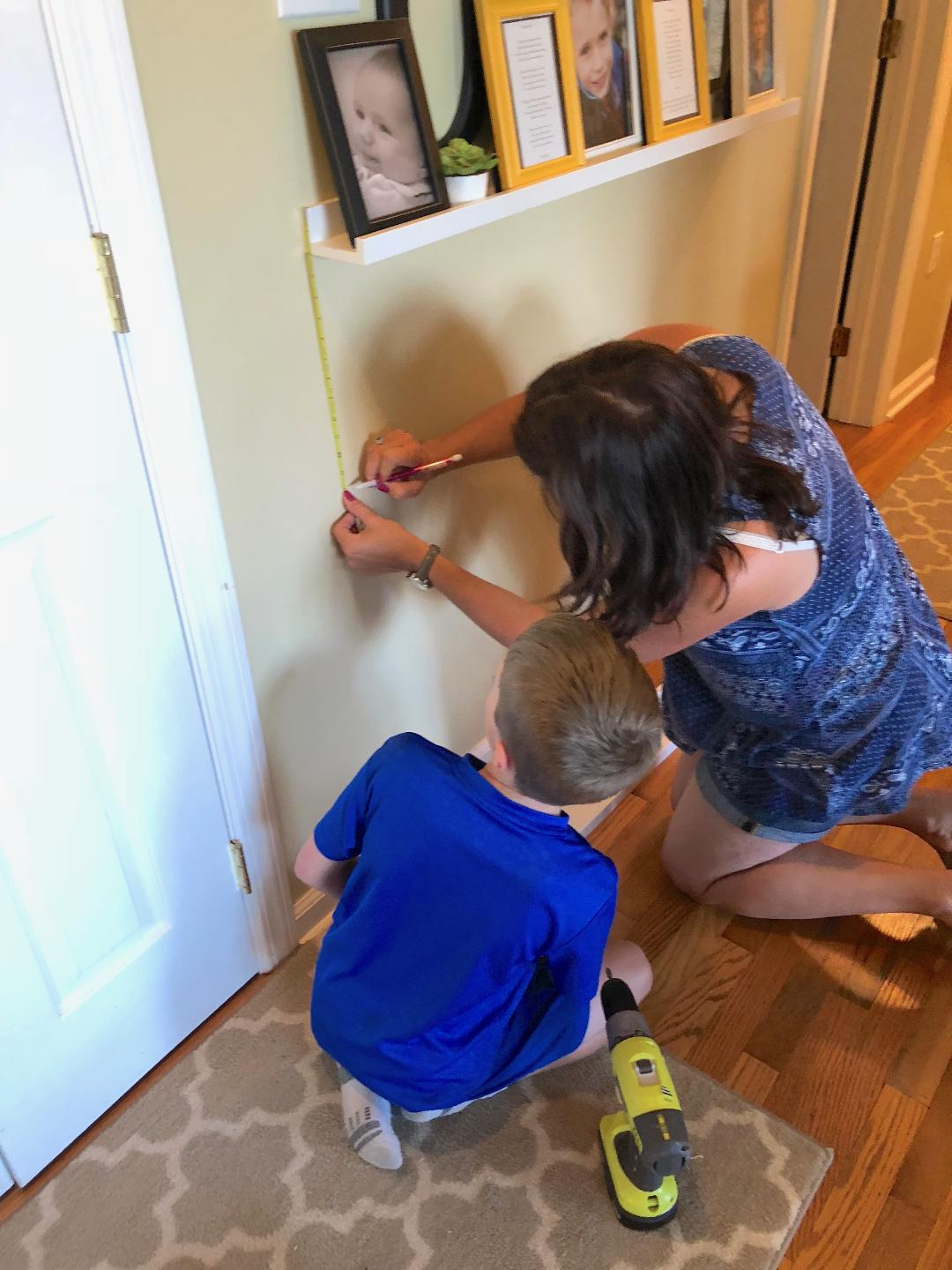 woman measuring for a gallery wall as son watches on