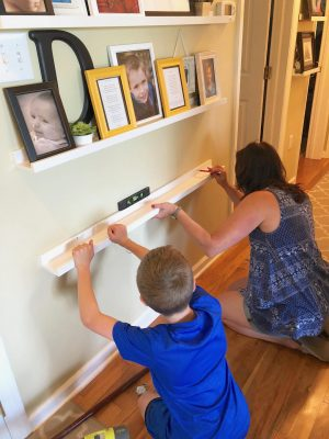 mom and son holding up a shelf while installing a gallery wall
