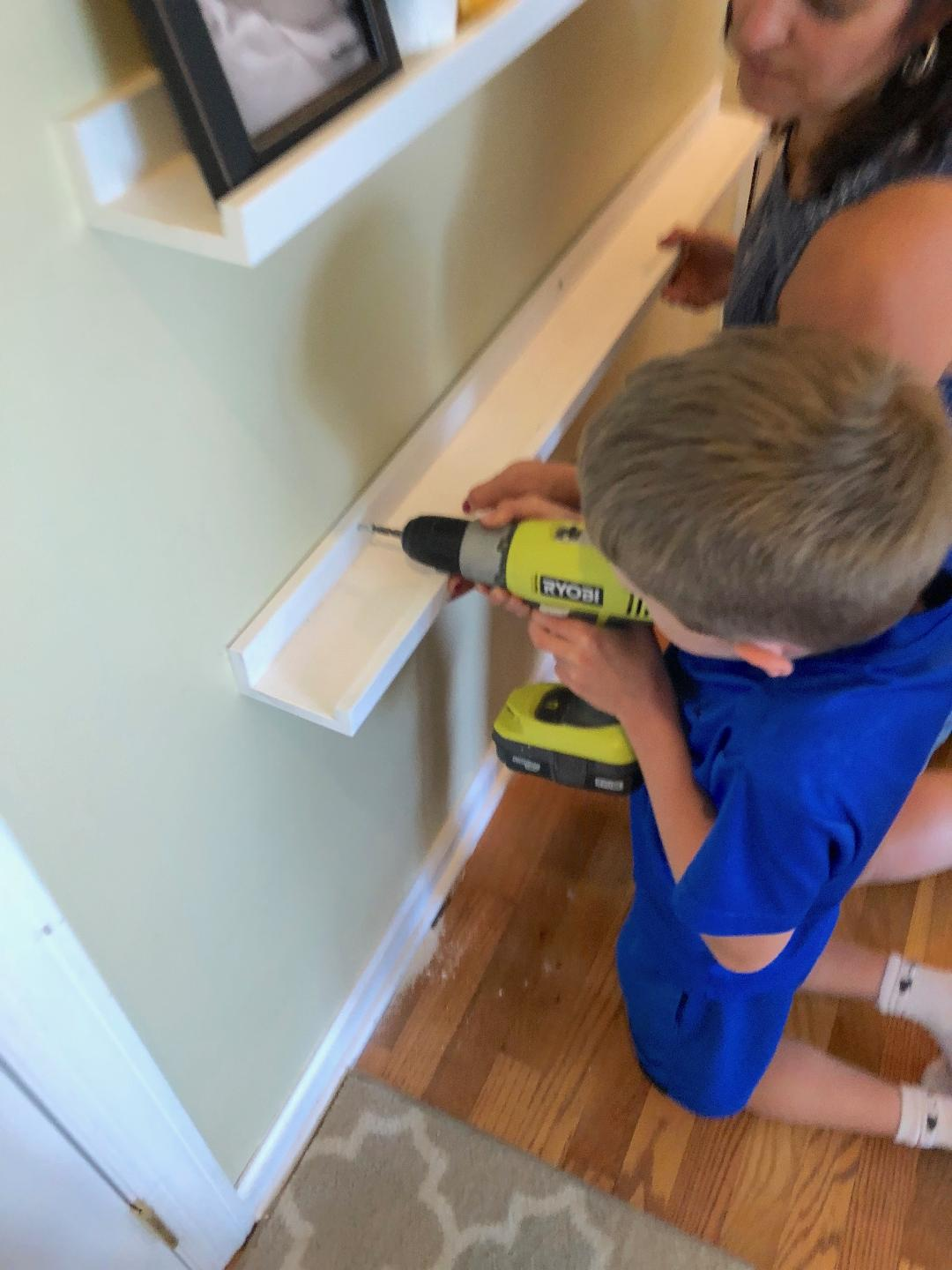 child using drill to insert screws into a shelf