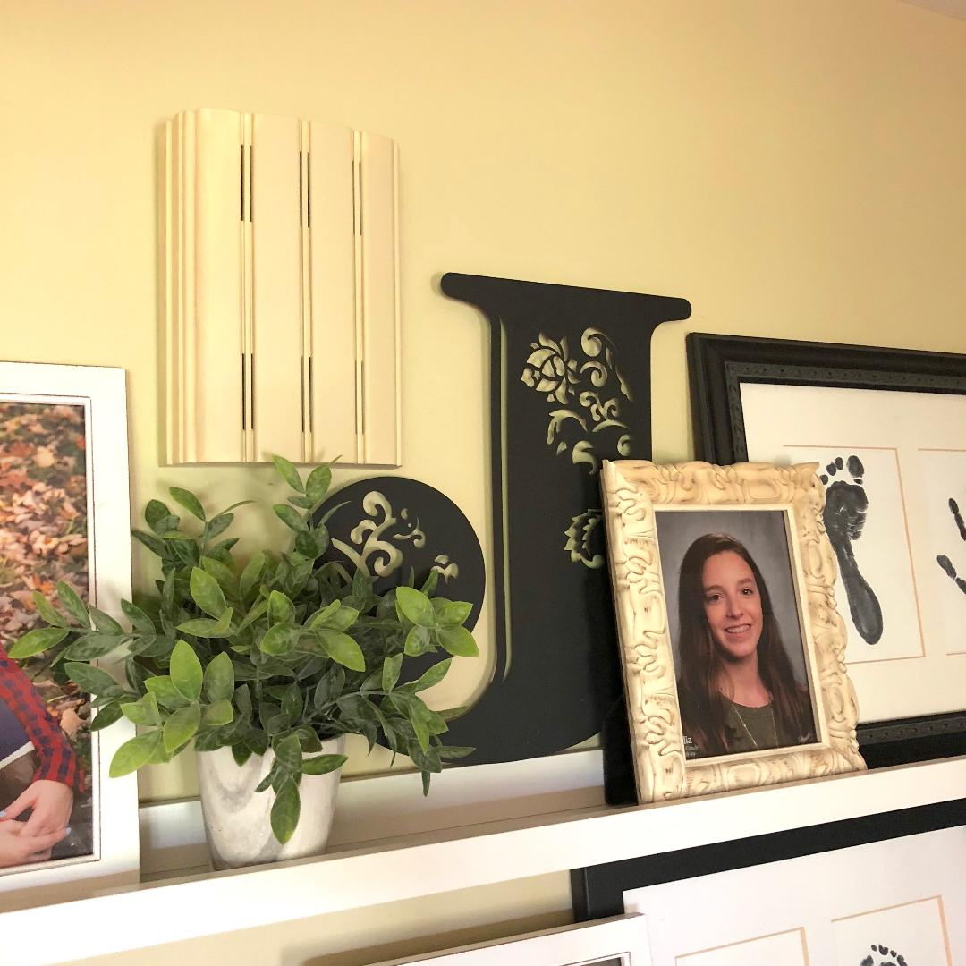 picture ledge adorned wiht photos and plant and decorative metal letter