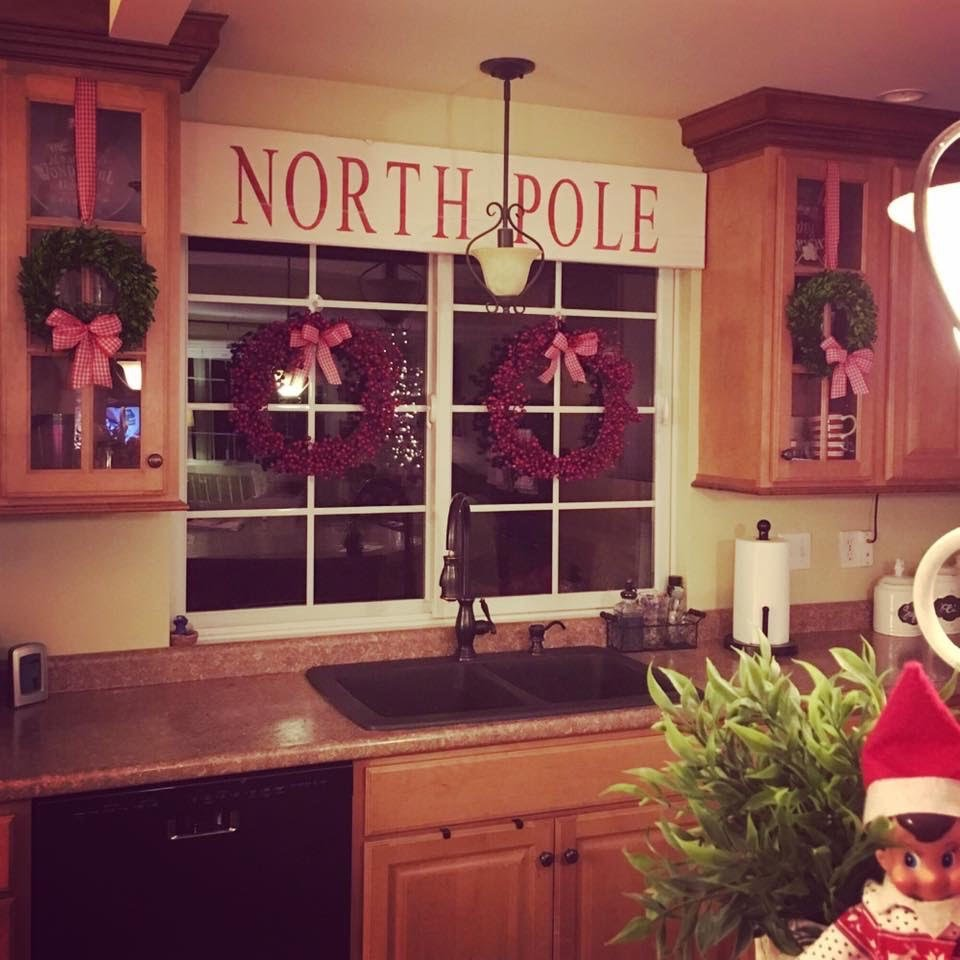 sign that says North Pole hung over the kitchen sink as a valance