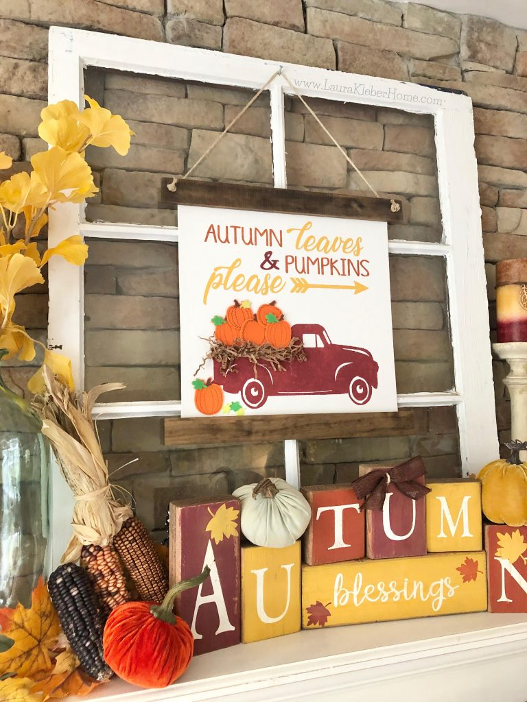 A close up of an old window with hanging Fall canvas banner sign, Fall letter blocks, and Fall colors including leaves and stems and candles and pumpkins)