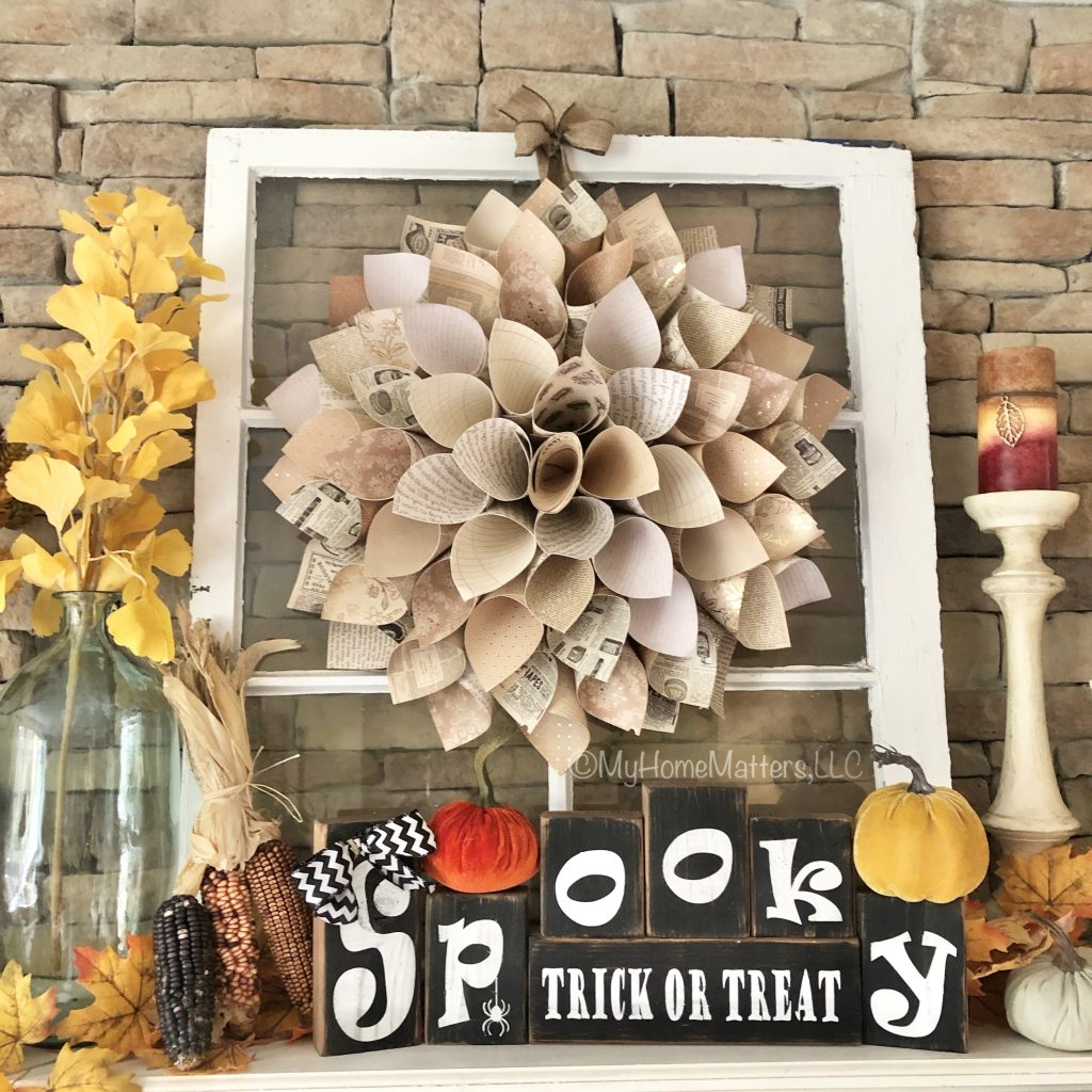to show the finished paper dahlia wreath hanging over a mantel