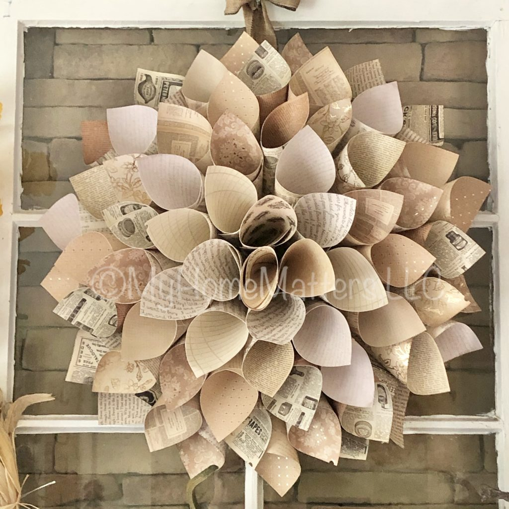 to show a paper dahlia wreath hung over an old window