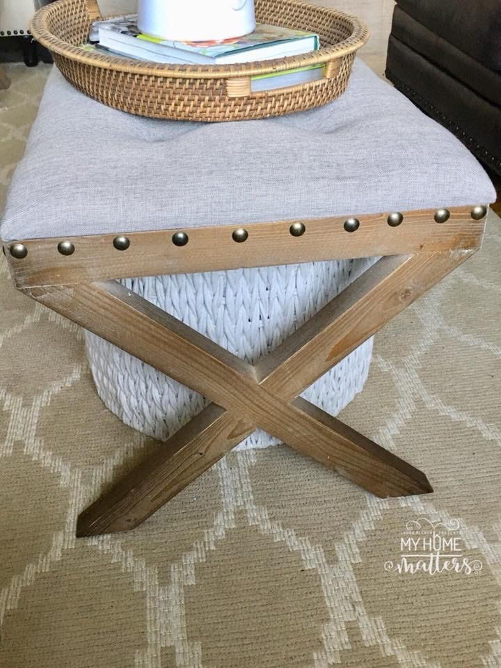 tufted bench used as a coffee table in living room