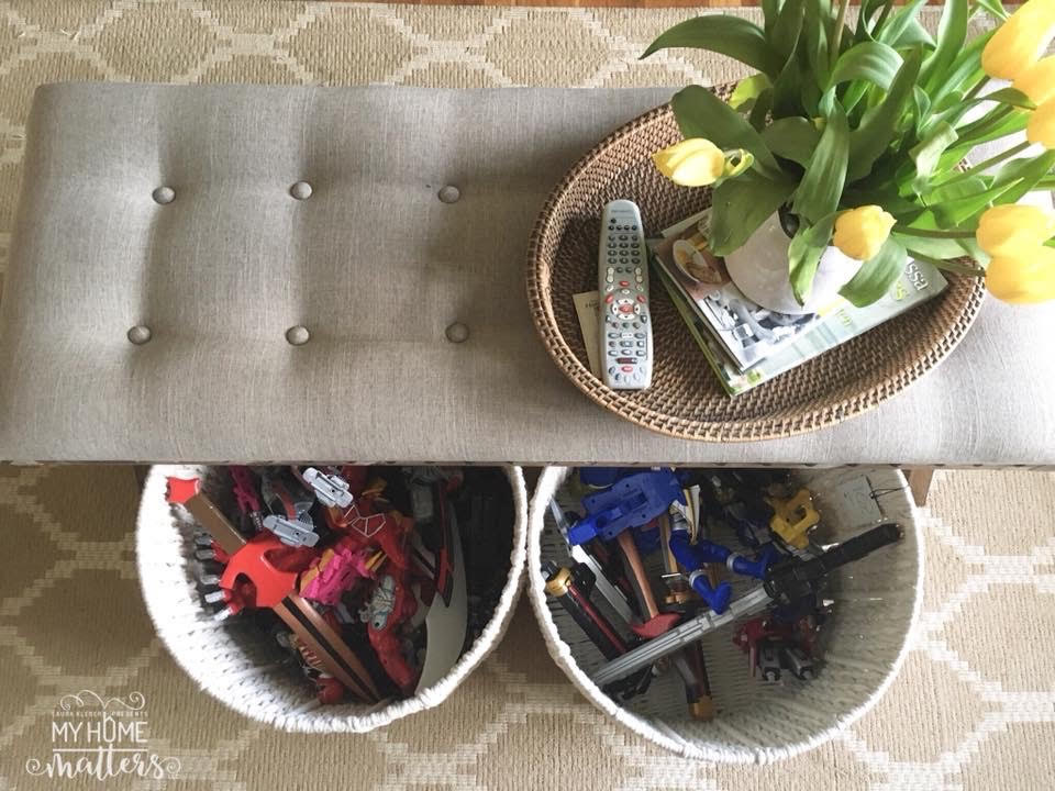 tufted bench used as living room coffee table with toy bin baskets below for storage