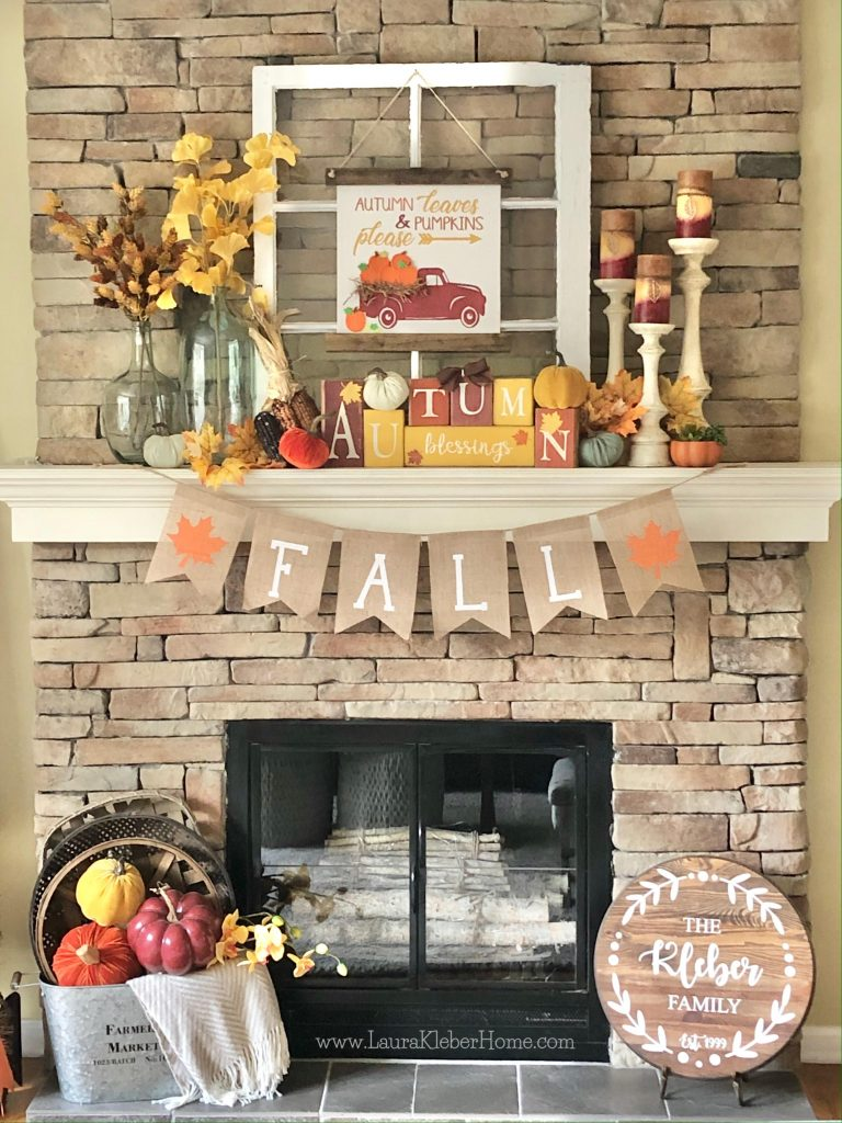A finished Fall mantel including fall stems and leaves in vases, a fall banner, fall candles, a fall canvas banner, wooden letter blocks, pumpkins and an old window