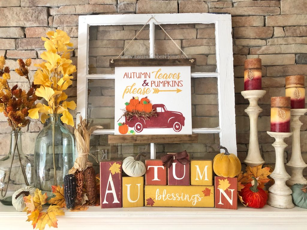 A finished example of a Fall mantel (showing vases with fall stems, fall letter blocks, dried corn, leaves, candle holders and festive fall candles, and pumpkins)