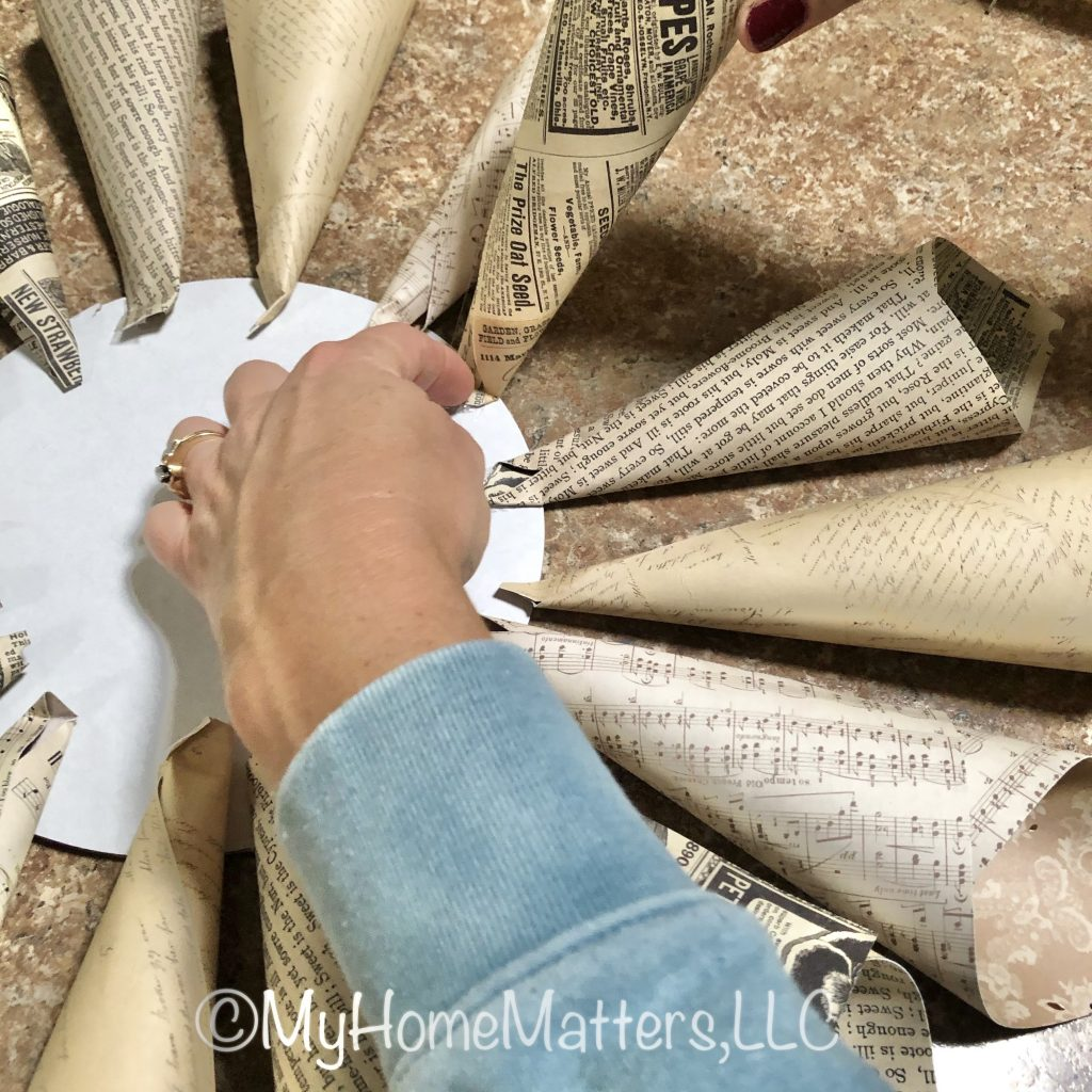 to show how to start gluing the cones to the cardboard back to make the paper dahlia wreath