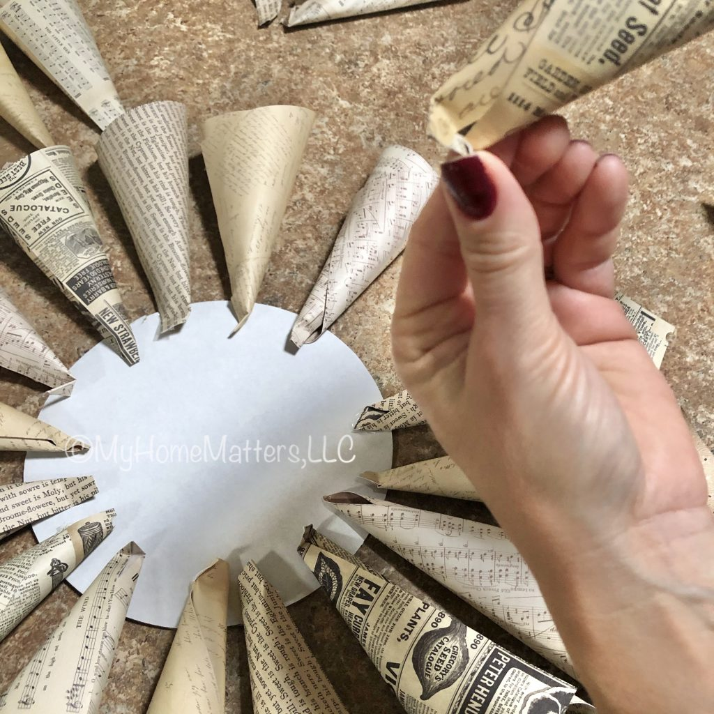 to show how to make the crease or fold on each cone for the paper dahlia wreath