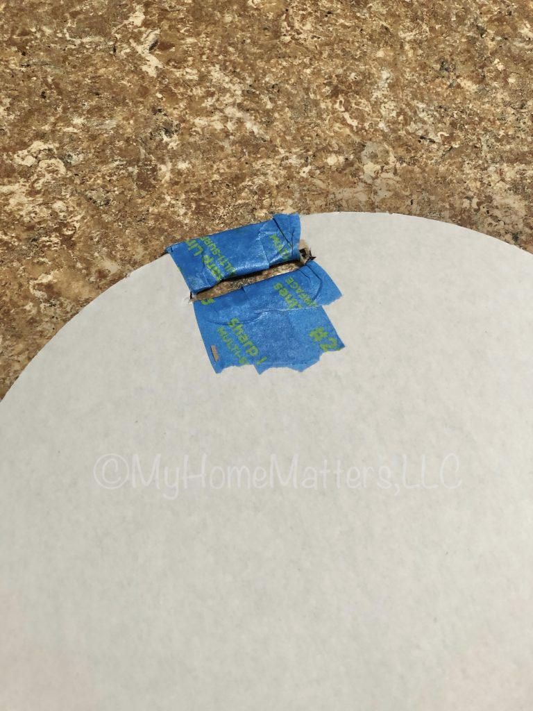 to show how to insert blue tape for protecting the slit needed for hanging the paper dahlia wreath