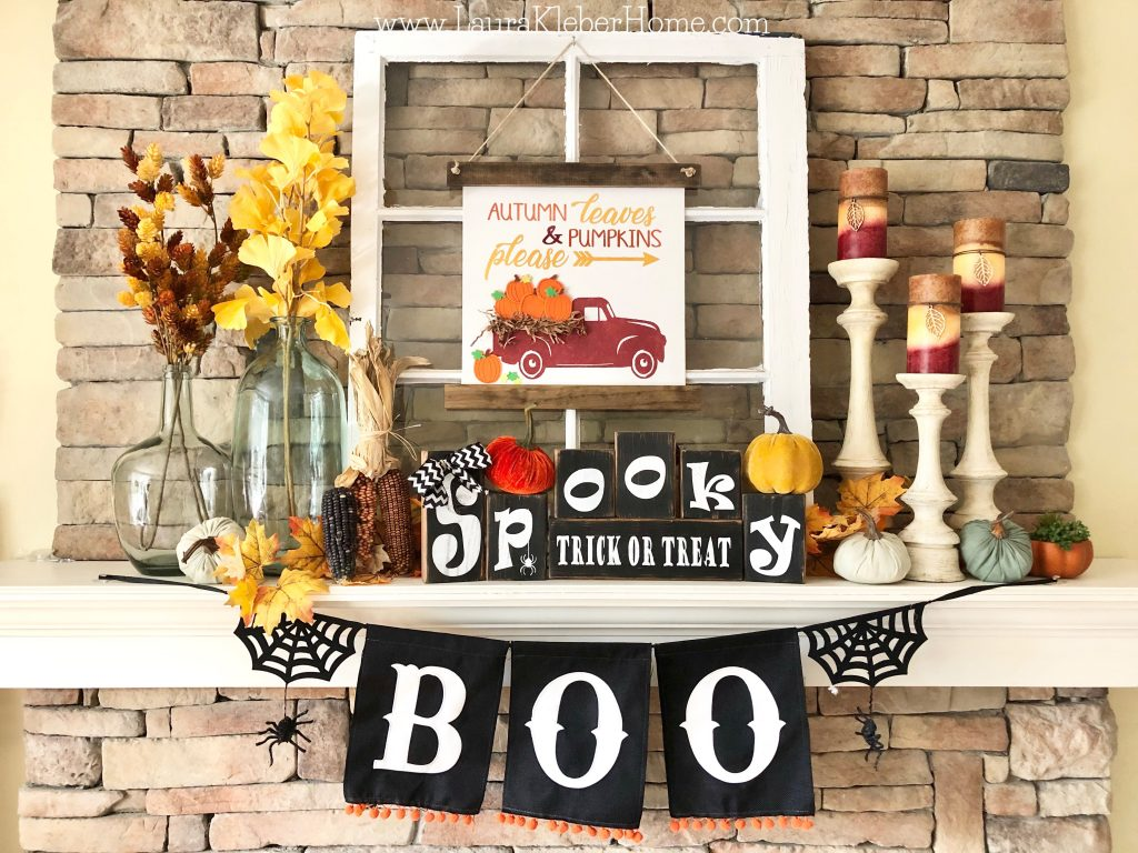 A finished Fall mantel that features Halloween wooden letter blocks, fall stems and leaves, fall candles, pumpkins, an old window, and a fall canvas banner