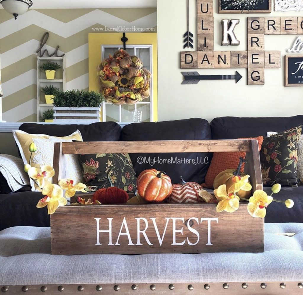 wooden toolbox used as decoration on coffee table bench, filled with pumpkins, fall living room decor