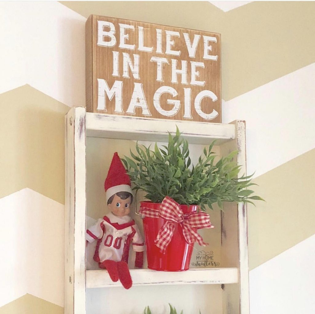 repurposed ladder hung on wall for decoration, accessorized with Christmas decorations such as elf on the shelf and Christmas decor