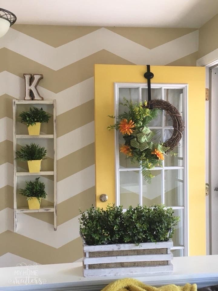 repurposed ladder used as a wall decoration in an entry way, chevron accent wall, yellow front door