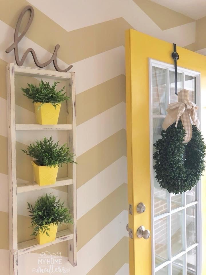 repurposed ladder used as wall decoration in entryway, chevron accent feature wall and yellow front door