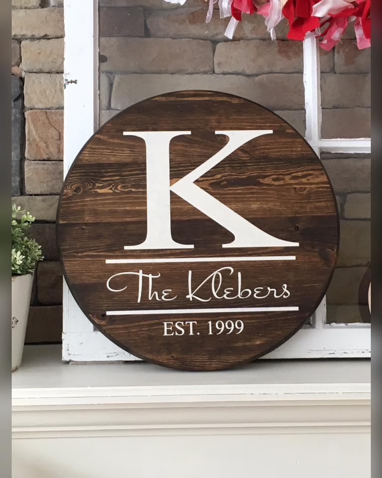 round wooden sign personalized with last name, initial and wedding date