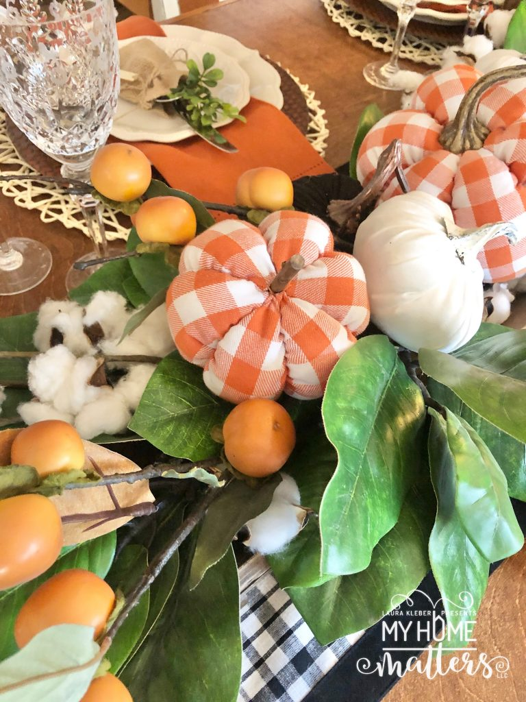 to show orange buffalo check pumpkins used to decorate a dining table