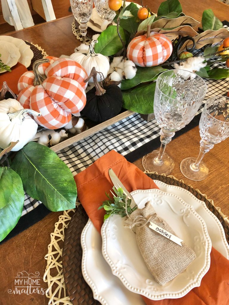 to show how to use orange buffalo check when decorating a dining table