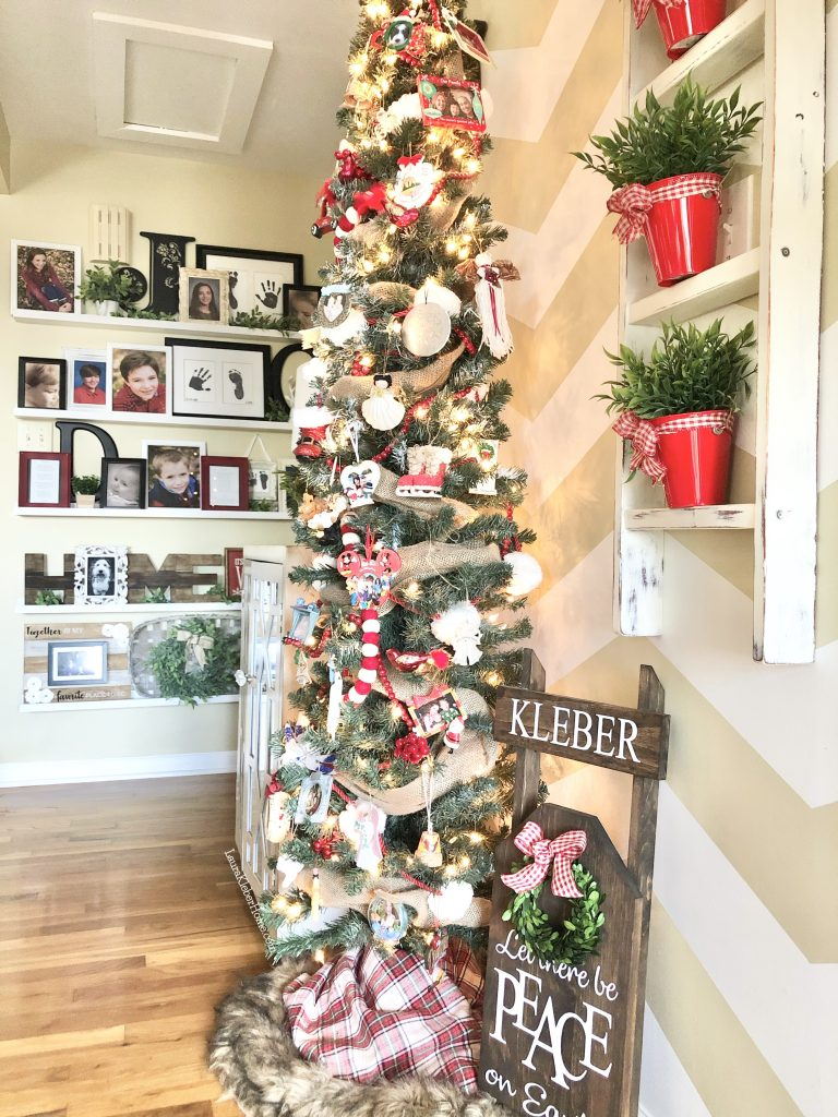 entry way decorated for Christmas with Christmas tree, wooden sled and wall collage