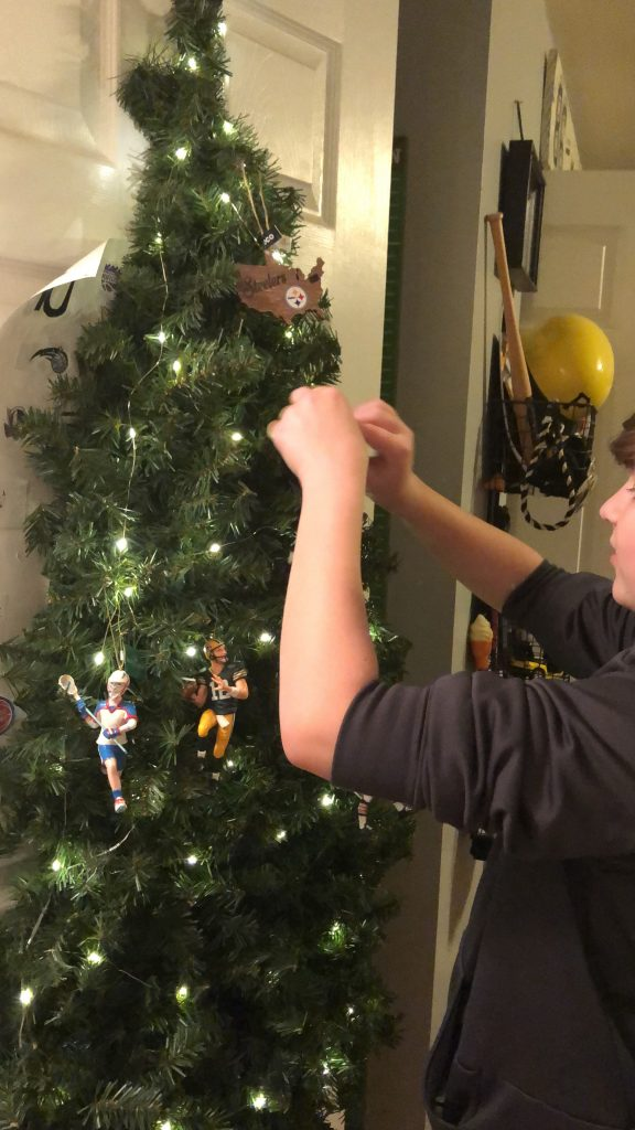 boy hanging ornaments on his Christmas tree