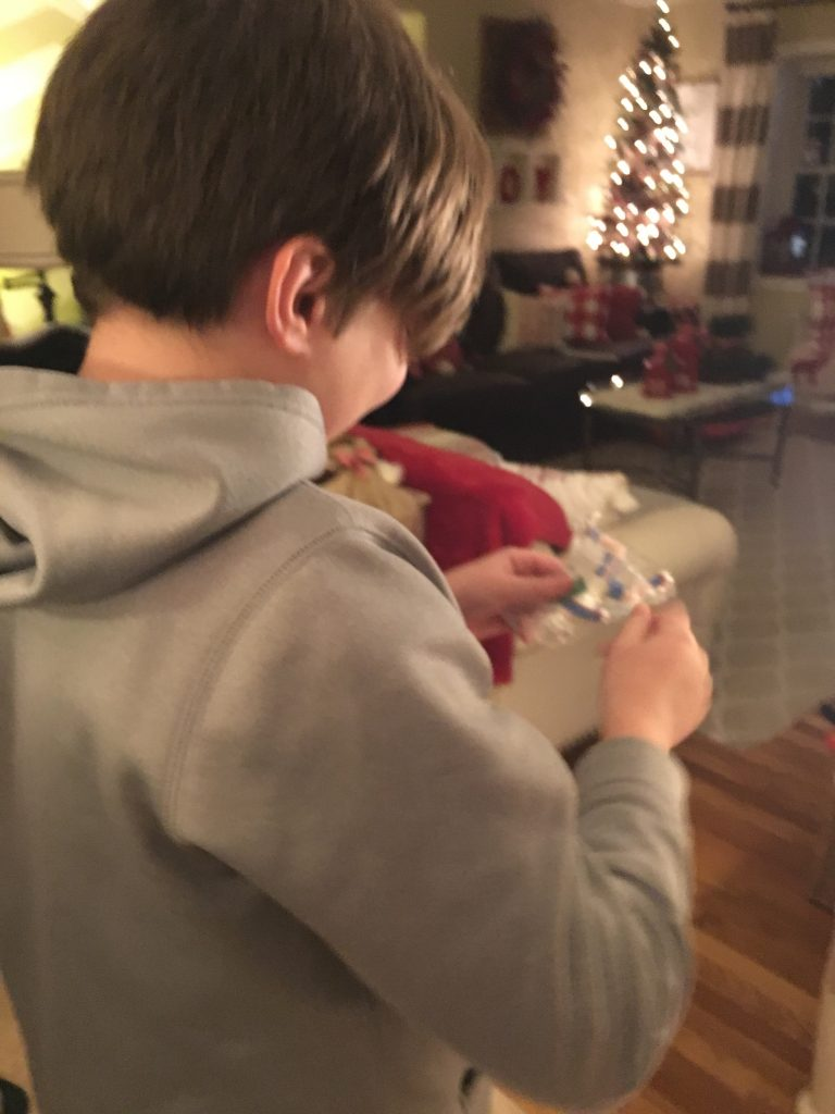 picture of a boy opening a Christmas  ornament