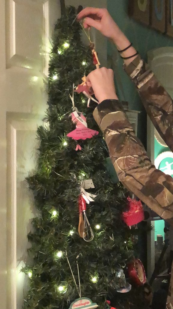 girl hanging ornaments on a Christmas tree