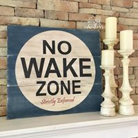 "planked wooden sign painted with ""no wake zone"""