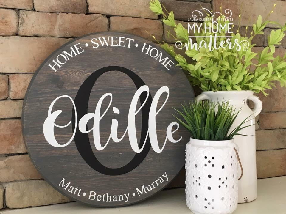 round wooden sign personalized with last name and home sweet home