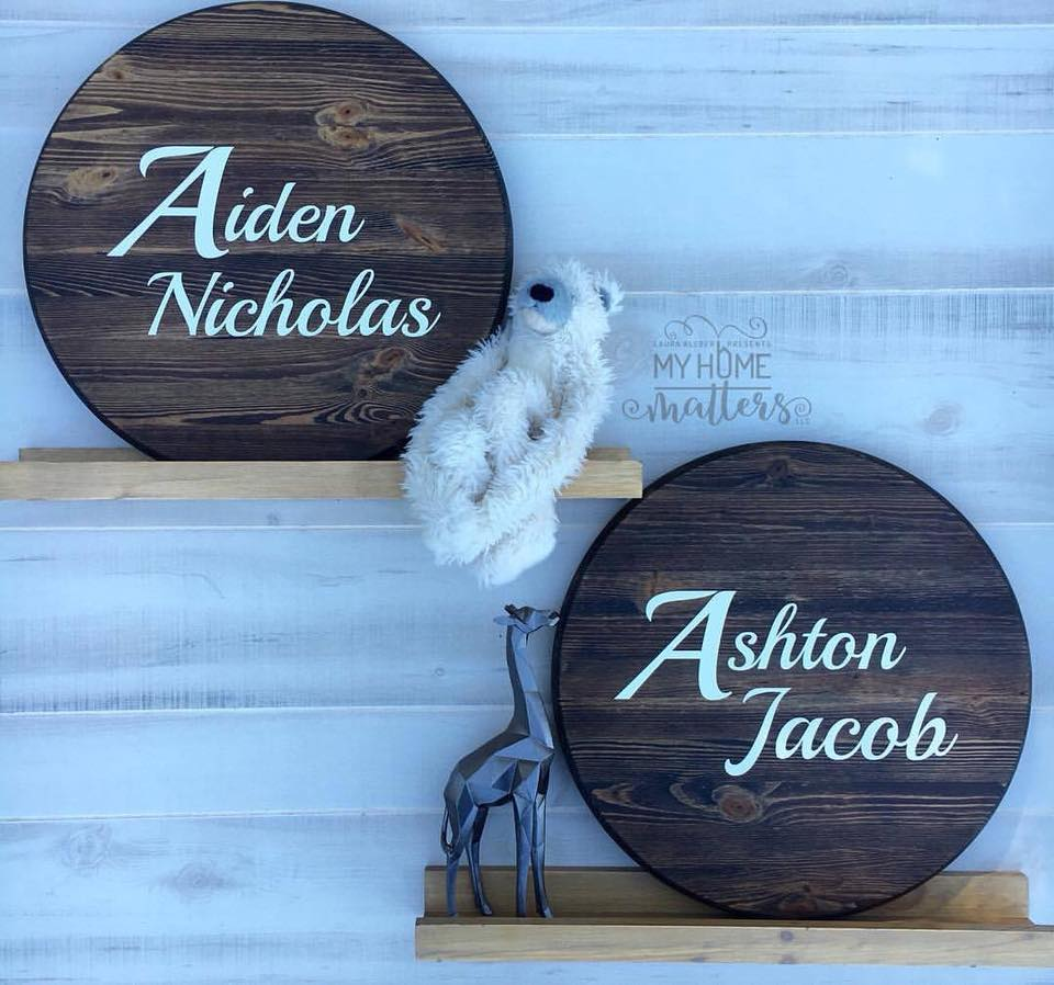 two round wooden signs personalized with boys' names