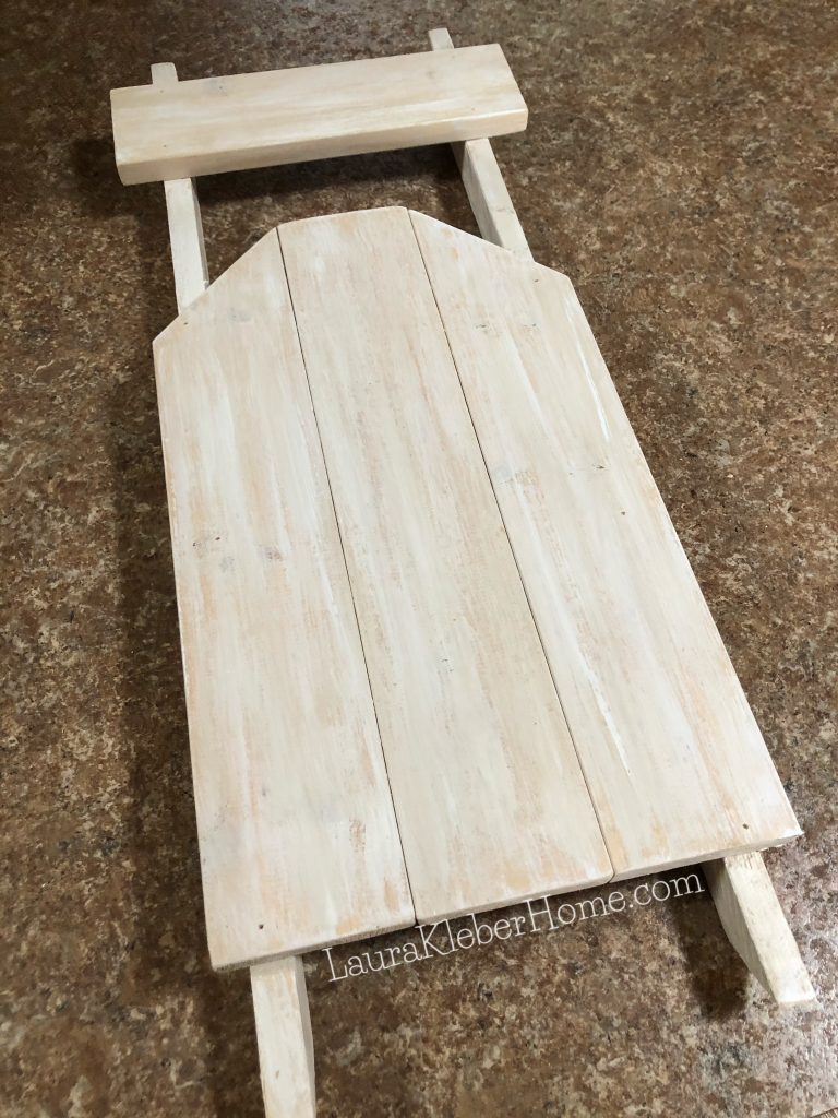 white and off white paint applied to a wooden sleigh
