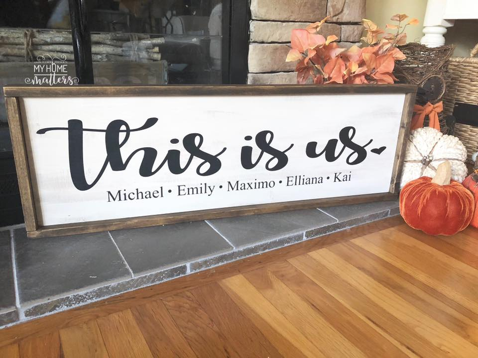 "framed wooden sign personalized with ""this is us"" and family names"