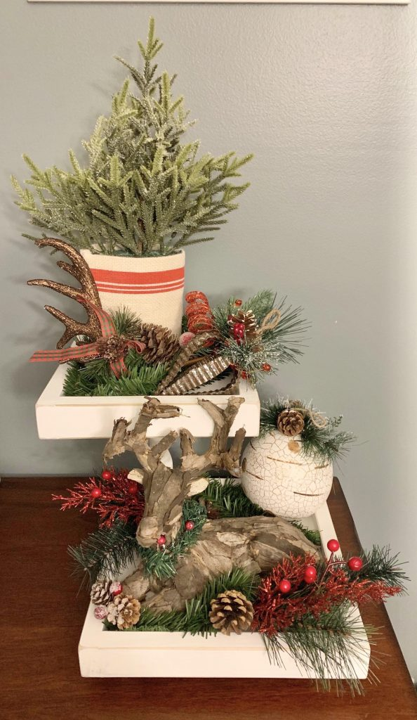 a tiered tray sitting on a dining room server decorated for Christmas