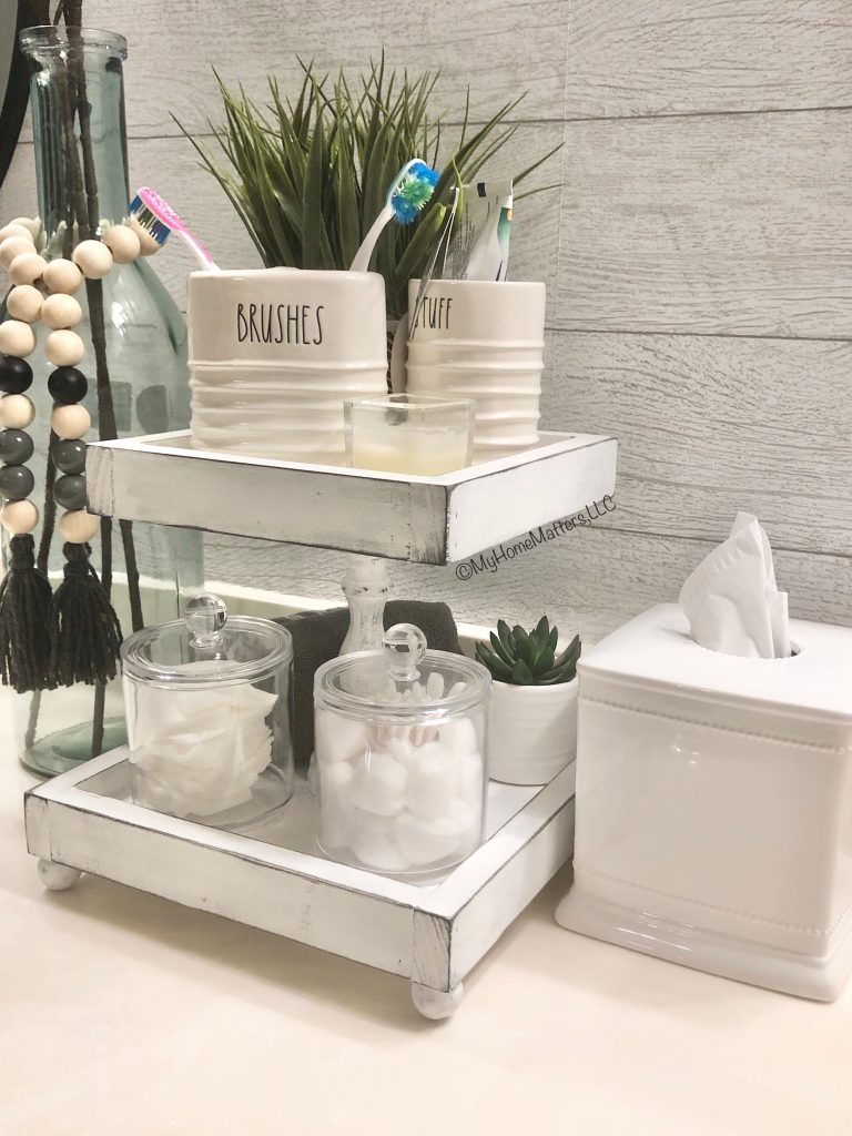 white tiered tray used for storage on a bathroom countertop
