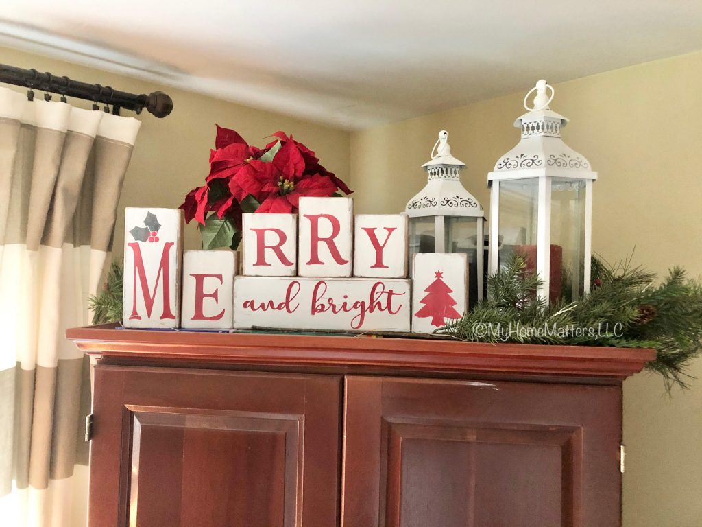 Letter blocks that spell out Merry and Bright sitting on top of a TV armoire