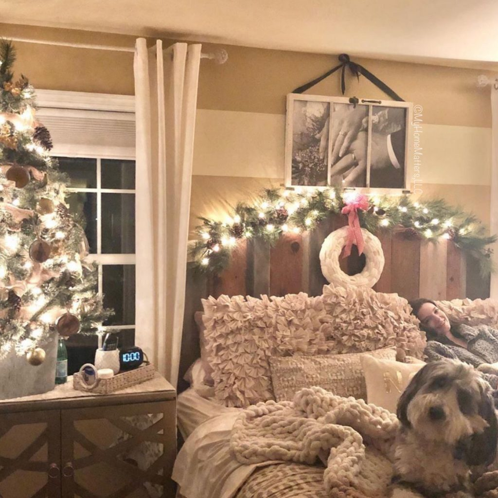 a a dog on a bed in a master bedroom decorated for Christmas and lit up at night