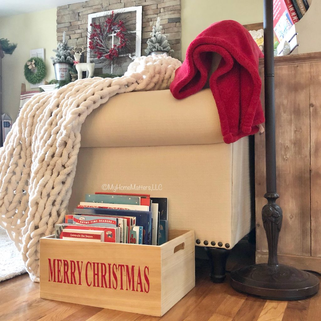 a wooden crate that holds a bunch of Christmas books beside a living room sofa