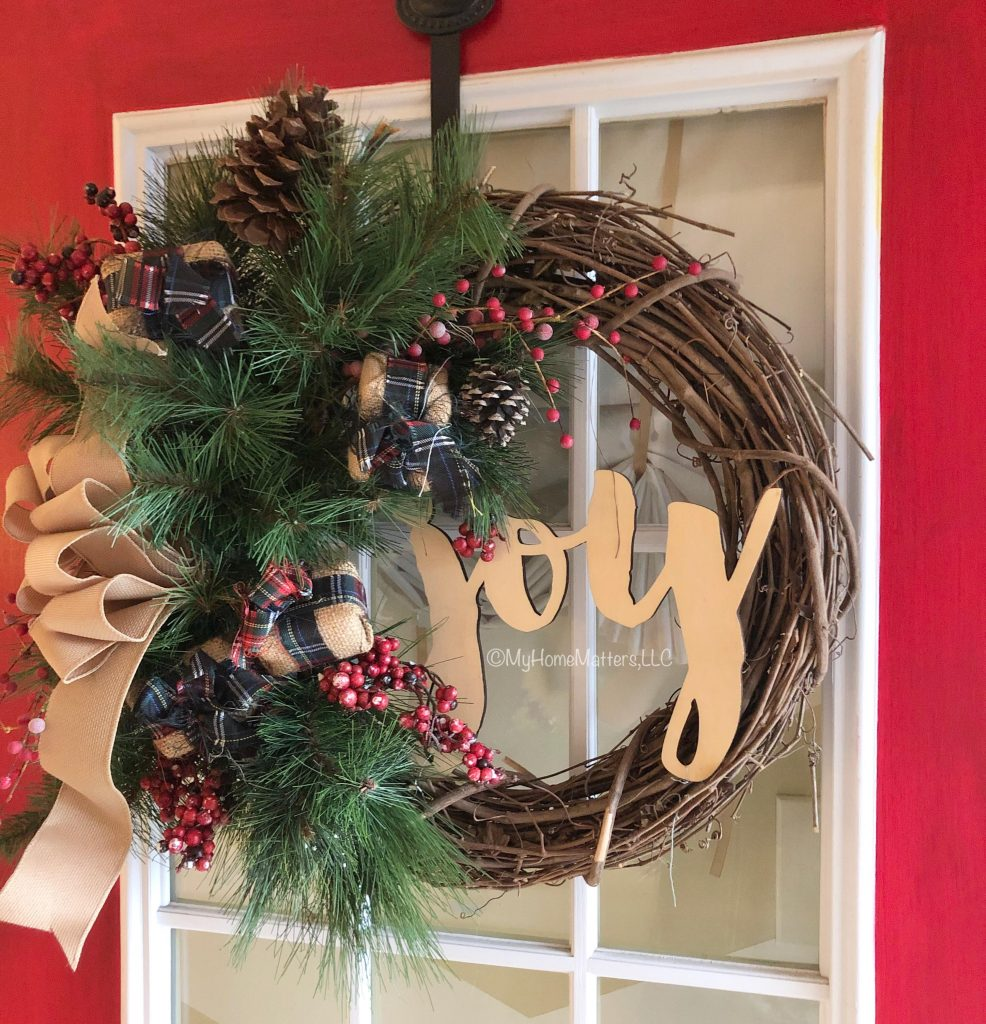 a red door with Christmas-inspired grapevine wreath on it