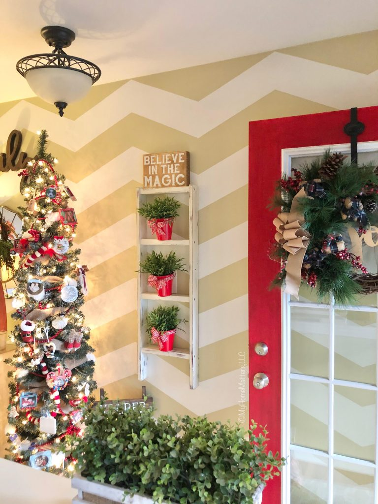an entryway that is decorated for Christmas including a red door and repurposed ladder