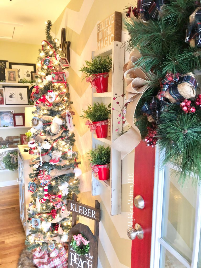 an entry way decorated for Christmas with a tree, old ladder and red door