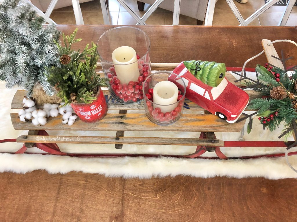 old sled used as a Christmas centerpiece on top of a dining table
