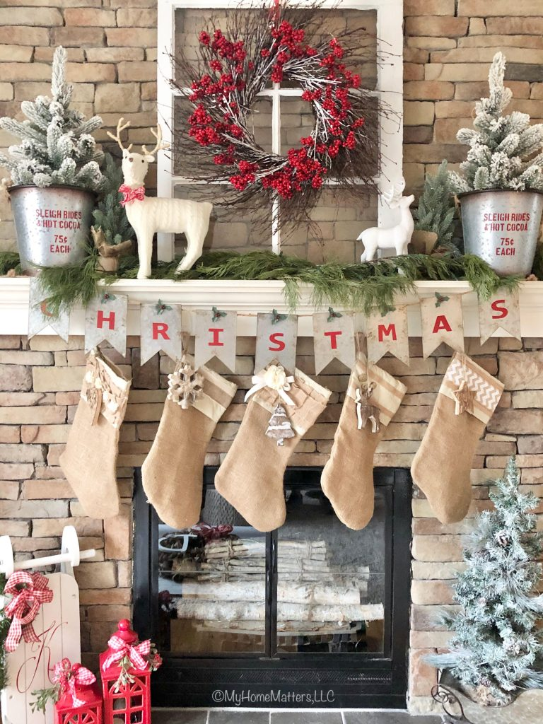 a mantel decorated for Christmas with burlap stockings and a Christmas banner
