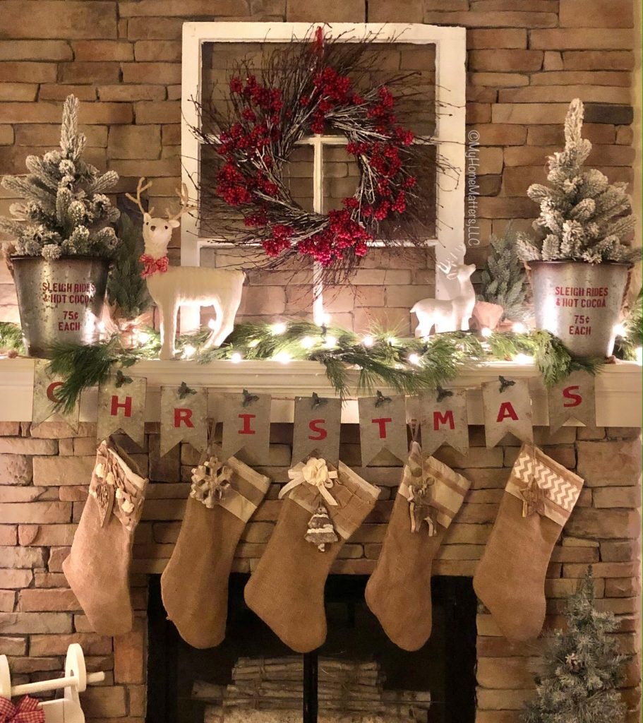 a mantel decorated for Christmas and lit up at night with lights