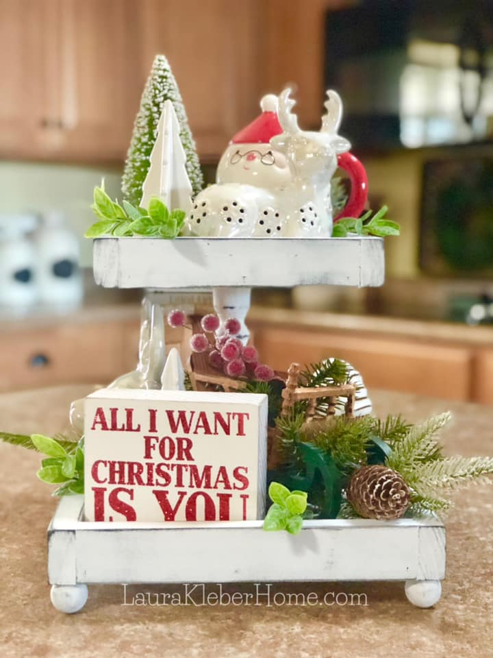 a tiered tray sitting on a kitchen island decorated with Christmas items