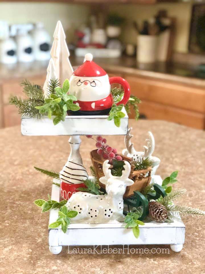 a tiered tray sitting on a kitchen island decorated for Christmas