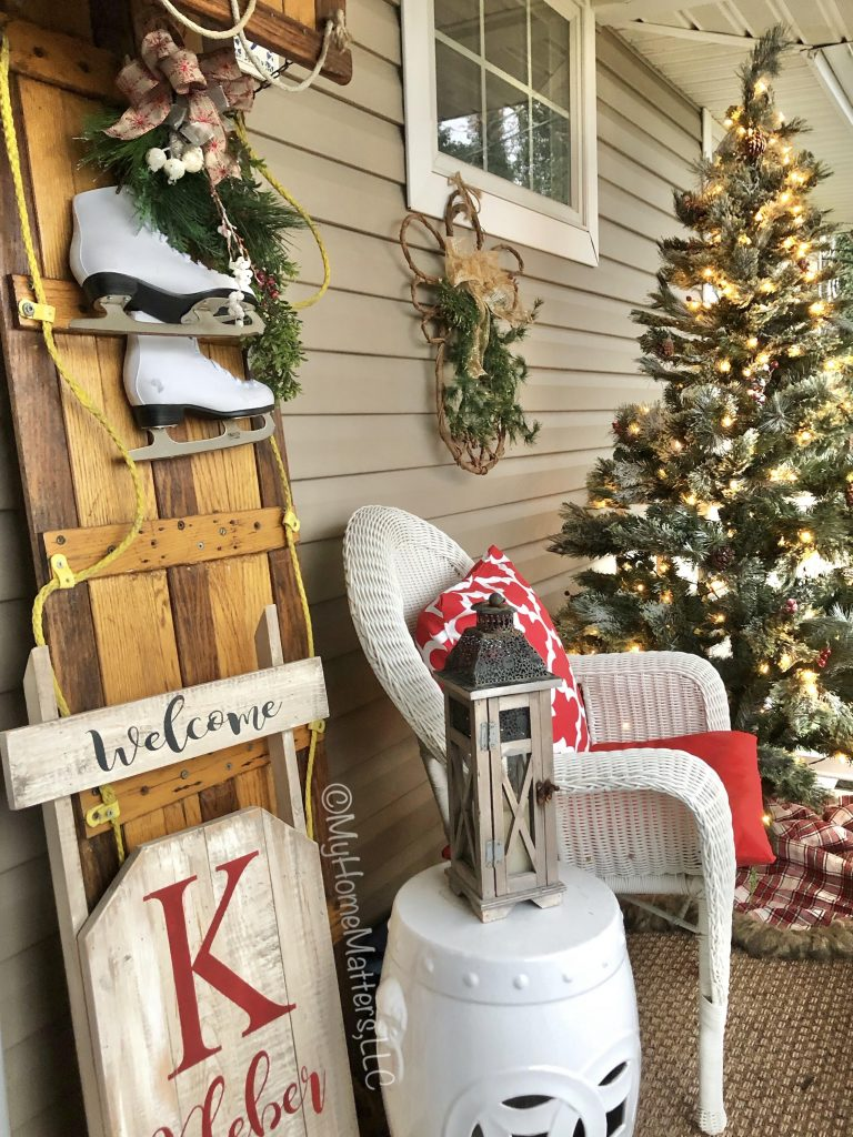 a front porch decorated for Christmas with a toboggan and Christmas tree