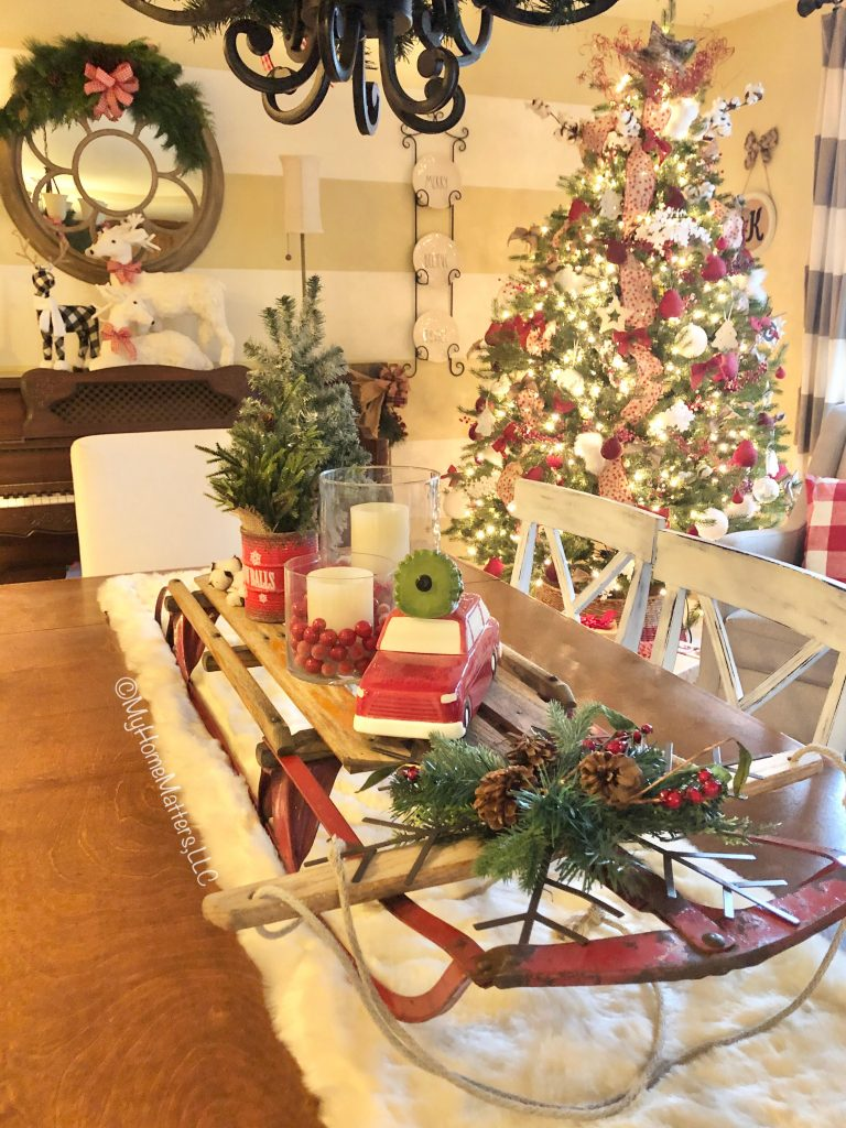 an old sled decorated for Christmas as a centerpiece on top of a dining table