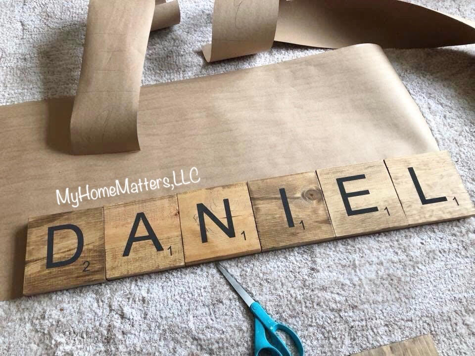 scrabble tiles being traced onto brown paper
